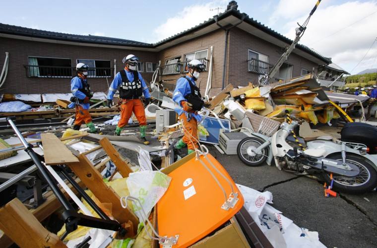 Rescuers check the damage area caused by earthquakes in Minamiaso, Kumamoto prefecture, Japan, Sunday, April 17, 2016. Two nights of increasingly terrifying earthquakes flattened houses and triggered major landslides in southern Japan. (AP Photo/Shizuo Kambayashi)