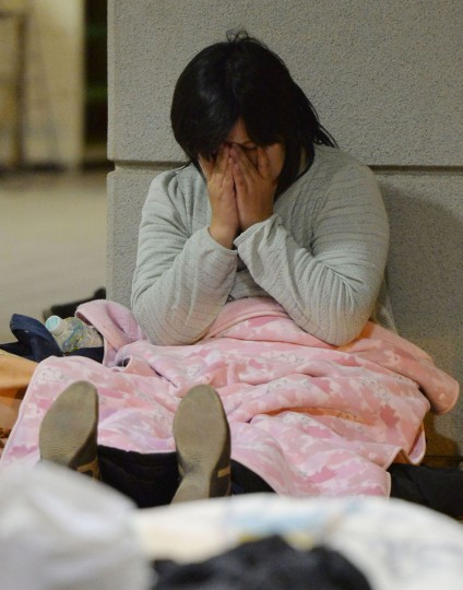 A woman covers her face at a shelter in Kumamoto, Japan Saturday, April 16, 2016. Powerful earthquakes a day apart shook southwestern Japan, as thousands of army troops and other rescuers on Saturday rushed to save scores of trapped residents before weather turns bad. (Ryosuke Ozawa/Kyodo News via AP)