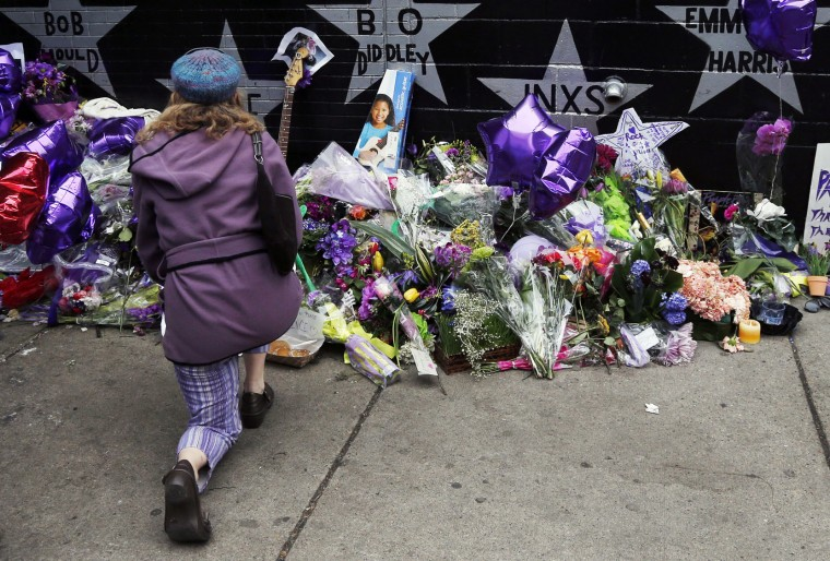 A woman kneels by the memorial at First Avenue Friday, April 22, 2016, in Minneapolis were Prince often performed. The pop super star died Thursday at the age of 57. (AP Photo/Jim Mone)