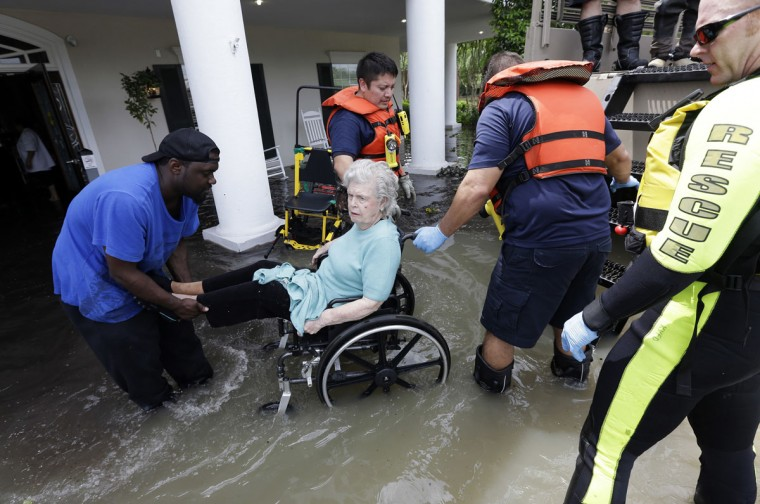 A resident of a retirement and assisted living complex is helped by rescue personnel as the facility is evacuated due to rising floodwaters Tuesday, April 19, 2016, in Spring, Texas. Storms have dumped more than a foot of rain in the Houston area, flooding dozens of neighborhoods. (AP Photo/David J. Phillip)