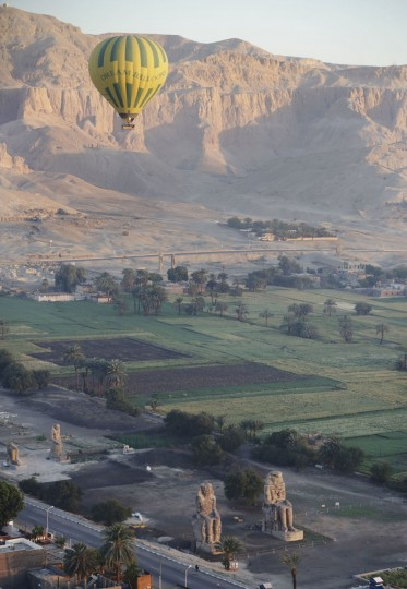 In this picture taken from a balloon Friday, April 1, 2016, a hot air balloon flies over the Colossi of Memnon on the west bank of the Nile River in Luxor, Egypt. Only from a balloon high in the sky, in the clear air of the early morning, can a visitor begin to grasp the beauty of antiquities on the ground in this one-time Egyptian capital once known as Thebes. The city in southern Egypt is one of the world's largest outdoor museums. (AP Photo/Amr Nabil)