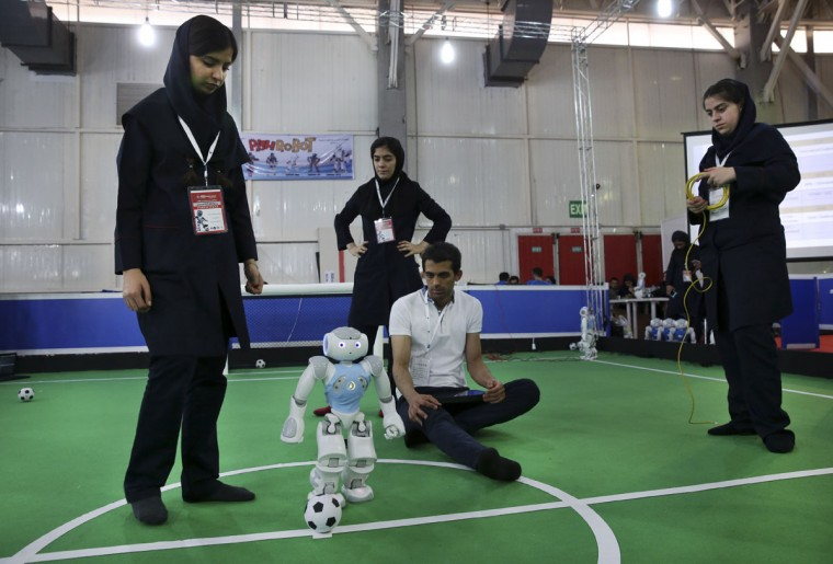 Iranian participants of the international robotics competition RoboCup Iran Open 2016, prepare their humanoid robot prior to a soccer match, in Tehran, Iran, Wednesday, April 6, 2016. The event, organized by Iranian RoboCup Regional Committee and Qazvin Azad University, was participated by 320 teams from Iran and abroad. The 3-day competitions kicked off on Wednesday at Tehran's Permanent Fairground. (AP Photo/Vahid Salemi)