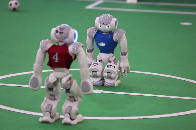 Robots from Iran's Qazvin Islamic Azad University and Germay's Nao-Team HTWK of Leipzig United University, takes part in a soccer match during the RoboCup Iran Open 2016, in Tehran, on April 6, 2016. (ATTA KENARE/AFP/Getty Images)