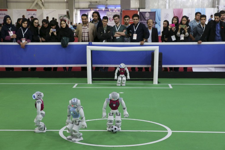 Humanoid robots from Iran GraceBand team, in blue, and Dainamite team from Germany play soccer while visitors follow the match during the international robotics competition, RoboCup Iran Open 2016, in Tehran, Iran, Wednesday, April 6, 2016. (AP Photo/Vahid Salemi)