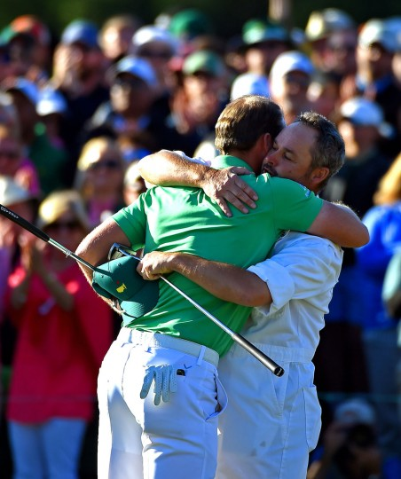 Danny Willett, left, is hugged by caddie Billy Foster after Willett sank his final putt on the 18th green during the final round of the Masters on Sunday, April 10, 2016, at Augusta National Golf Club in Augusta, Ga. (Jeff Siner/Charlotte Observer/TNS)