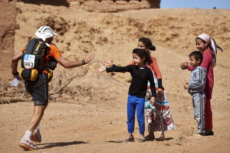 A competitor taking part in the 31st edition of the Marathon des Sables is greeted by children in the village of Taouz on April 11, 2016 in the southern Moroccan Sahara desert. (JEAN-PHILIPPE KSIAZEK/AFP/Getty Images)