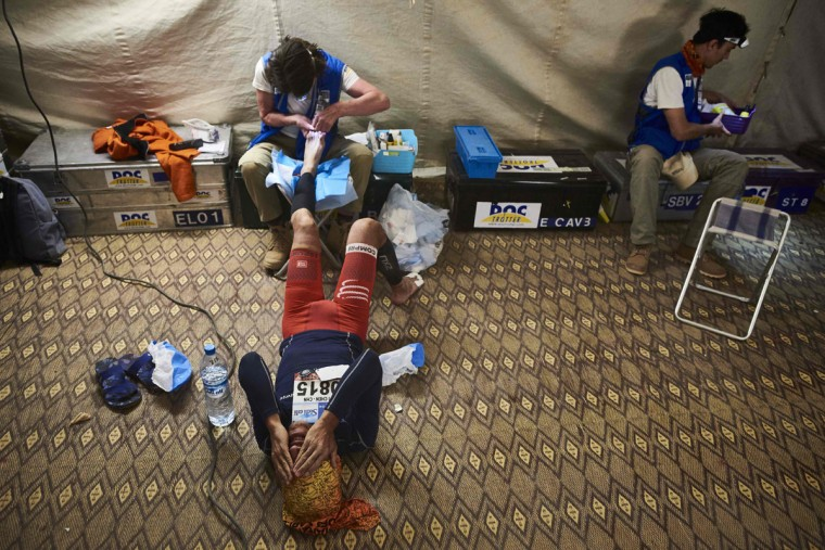 A competitor receives treatment for their feet at the end of the third stage of the 31st edition of the Marathon des Sables On April 12, 2016 in the southern Moroccan Sahara desert. (JEAN-PHILIPPE KSIAZEK/AFP/Getty Images)