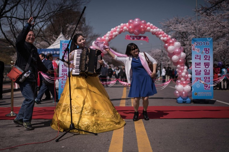 In a photo taken on April 5, 2016 tourists dance with a musician beneath cherry blossoms on Yeouido island in Seoul. The annual cherry blossom festival on Yeouido island in central Seoul runs from April 1-10. (ED JONES/AFP/Getty Images)
