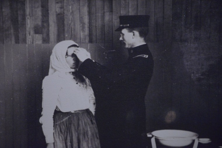 "An archival photo at the Immigration Museum shows an immigrant wearing a head scarf being screened for trachoma, an eye infection. Immigrants had to pass multiple tests before being allowed to stay in Baltimore -- including an ""imbecile test."" Those who failed were sent back to Europe."
