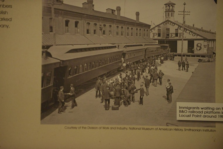 A photograph of migrants at the Locust Point train station; though some stayed in Baltimore, many more continued their travels West via the Baltimore and Ohio railroad. From Europe, a prospective migrant could purchase a door-to-door trip that included land and sea transportation to a new life in the United States. (Christina Tkacik/Baltimore Sun).