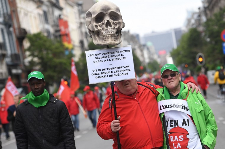 """A demonstrator holds a placard reading """"This is the future of our social insurance"""", during a national anti-austerity protest on May 24, 2016, in Brussels. Belgian trade unions called for mass protests against the centre-right government's proposed work reforms as they plan rallies and strikes over the next few months. / (Dirk Waem/AFP/Getty Images)"""
