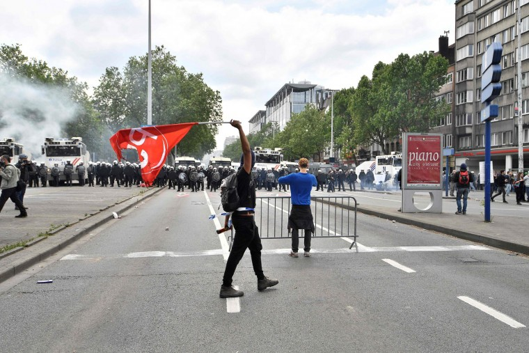A hodded man walks and brandishes a flag of the Belagian socialist party as Belgium's riot police stand guard during a national anti-austerity demonstration on May 24, 2016, in Brussels Belgian trade unions called for mass protests against the centre-right government's proposed work reforms as they plan rallies and strikes over the next few months. (Dirk Waem/AFP/Getty Images)
