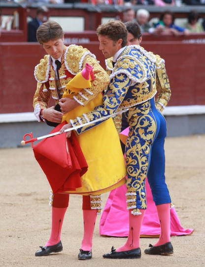 French matador Juan Leal (L) is handed a small red cape or muleta, after using a dress cape or capote during the San Isidro Feria at Las Ventas bullring in Madrid on May 17, 2016. (Alberto Simon/AFP/Getty Images)