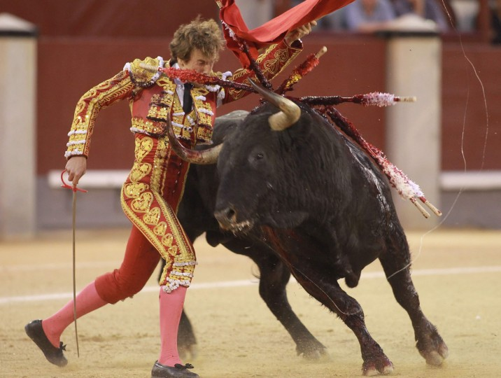 """Spanish matador Roman performs a pass with """"muleta"""" to a bull during the San Isidro Feria at Las Ventas bullring in Madrid on May 19, 2016. (Alberto Simon/AFP/Getty Images)"""