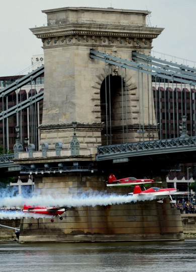 Hungarian aerobatics pilot and European champion air racer Zoltan Veres and his teammates, Jason Beamish and Larry Beamish, fly under the oldest Hungarian bridge, the 'Chain Bridge' and over the Danube River in Budapest on May 1, 2016 during their Guinness record attempt. (ATTILA KISBENEDEK/AFP Getty Images)