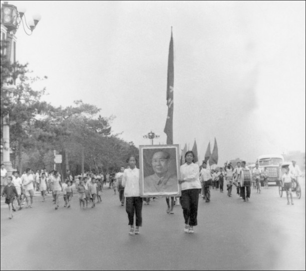 "This file photo taken in June 1966 shows a propaganda squad of Red Guards, high school and university students, carrying a portrait of Chairman Mao Zedong as they parade on Chang'an avenue in Beijing to spread Mao's thought during the ""Great Proletarian Cultural Revolution."" Launched by Mao in 1966 to topple his political enemies after the failure of the Great Leap Forward, the Cultural Revolution saw a decade of violence and destruction nationwide as party-led class conflict devolved into social chaos. (AFP PHOTO / JEAN VINCENT)"