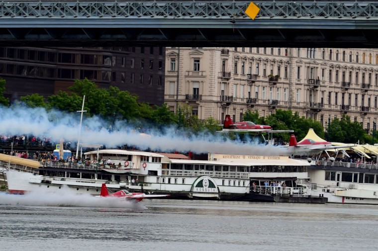 Hungarian aerobatics pilot and European champion air racer Zoltan Veres and his teammates, Jason Beamish and Larry Beamish, fly in team under the oldest Hungarian bridge, the 'Chain Bridge' and over the Danube River in Budapest on May 1, 2016 during their Guinness record attempt. (ATTILA KISBENEDEK/AFP/Getty Images)
