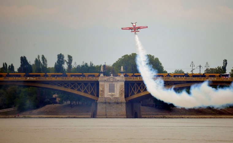 Hungarian aerobatics pilot and European champion air racer Zoltan Veres presents his exercise in front of the Margit Bridge over the Danube River in Budapest on May 1, 2016. (ATTILA KISBENEDEK/AFP/Getty Images)