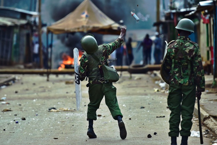 A riot policeman throws a teargas grenade at protestors during a demonstration of opposition supporters protesting for a change of leadership at the electoral commission ahead of a vote due next year, in Kibera slum, Nairobi on May 23, 2016. Local media reported at least one killed in Kisumu in the west of the country, while police in Nairobi and the second city of Mombasa fought running battles with small groups of protesters.There was no immediate police confirmation of the reported death. Police had banned the planned demonstrations and scores of officers in riot gear guarded the building that houses the election commission headquarters in the centre of the capital. (AFP PHOTO / CARL DE SOUZA)