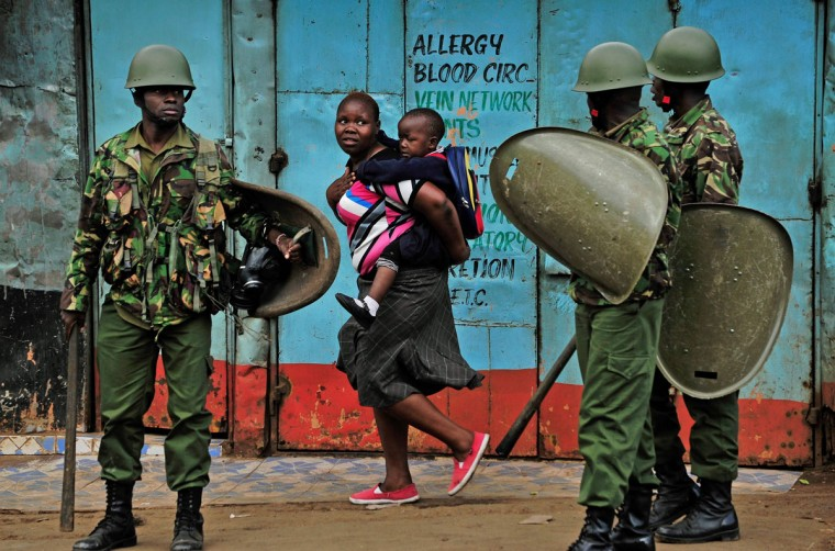 A woman carrying a child walks past riot policemen as they stand guard during a demonstration of opposition supporters protesting for a change of leadership at the electoral commission ahead of a vote due next year, in Kibera slum, Nairobi on May 23, 2016. Local media reported at least one killed in Kisumu in the west of the country, while police in Nairobi and the second city of Mombasa fought running battles with small groups of protesters.There was no immediate police confirmation of the reported death. Police had banned the planned demonstrations and scores of officers in riot gear guarded the building that houses the election commission headquarters in the centre of the capital. (AFP PHOTO / KEVIN MIDIGO)