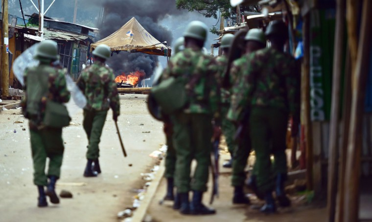 Riot policemen walk towards a burning barricade in Kibera slum, Nairobi on May 23, 2016 during a demonstration of opposition supporters protesting for a change of leadership at the electoral commission ahead of a vote due next year. Local media reported at least one killed in Kisumu in the west of the country, while police in Nairobi and the second city of Mombasa fought running battles with small groups of protesters. There was no immediate police confirmation of the reported death. Police had banned the planned demonstrations and scores of officers in riot gear guarded the building that houses the election commission headquarters in the centre of the capital. (AFP PHOTO / CARL DE SOUZA)