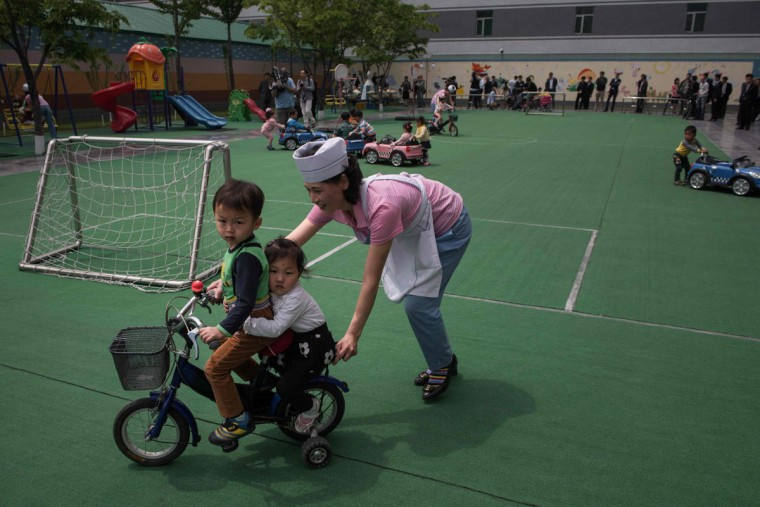 A carer pushes two children on a bicycle at a day care centre for children of workers at a silk factory in Pyongyang on May 9, 2016. (AFP PHOTO / Ed Jones)