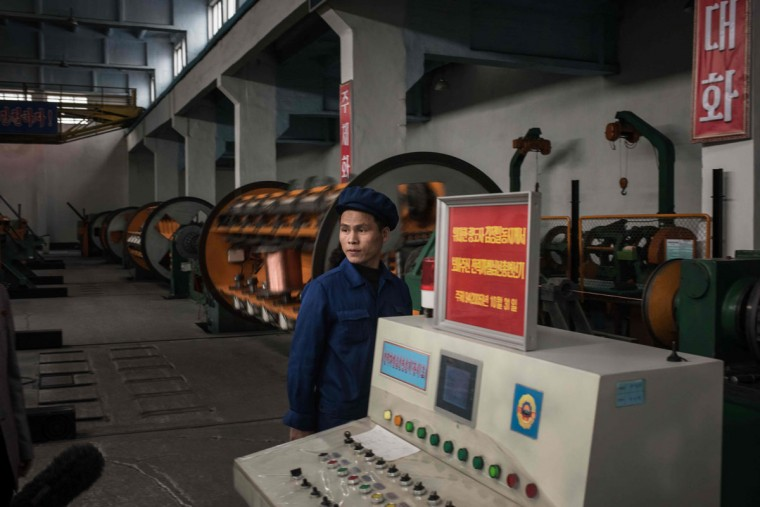 A worker stands before machinery during a media tour of the March 26 Electric Cable Factory in Pyongyang on May 6, 2016. When one of the world's most secretive states opens the door to the international media, it keeps a firm grip on the handle. Some 130 journalists flocked to North Korea at the express invitation of the Pyongyang authorities to cover the opening of a rare ruling party congress. They got within 200 meters of the venue, the April 25 Palace, and that was where they were stopped -- on the other side of the road, under a steady drizzle that had been falling on the capital all morning. Instead of a rare glimpse of the country's highest-level political meeting for almost four decades, the media were then offered a tour of the March 26 Electric Cable Factory. North Korea issues reporting visas sparingly and escorts all journalists to make sure it sets the agenda and gets its point across. (AFP PHOTO / Ed JonesED JONES/AFP/Getty Images)