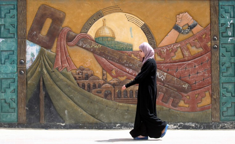 "A Palestinian woman walks past a mural in the Khan Yunis refugee camp in the southern Gaza Strip on May 15, 2016, on the 68th anniversary of the ""Nakba"". ""Nakba"" means in Arabic ""catastrophe"" in reference to the birth of the state of Israel 68-years-ago in British-mandate Palestine, which led to the displacement of hundreds of thousands of Palestinians who either fled or were driven out of their homes during the 1948 war over Israel's creation. The key symbolises the homes left by Palestinians in 1948. (AFP PHOTO / SAID KHATIB)"