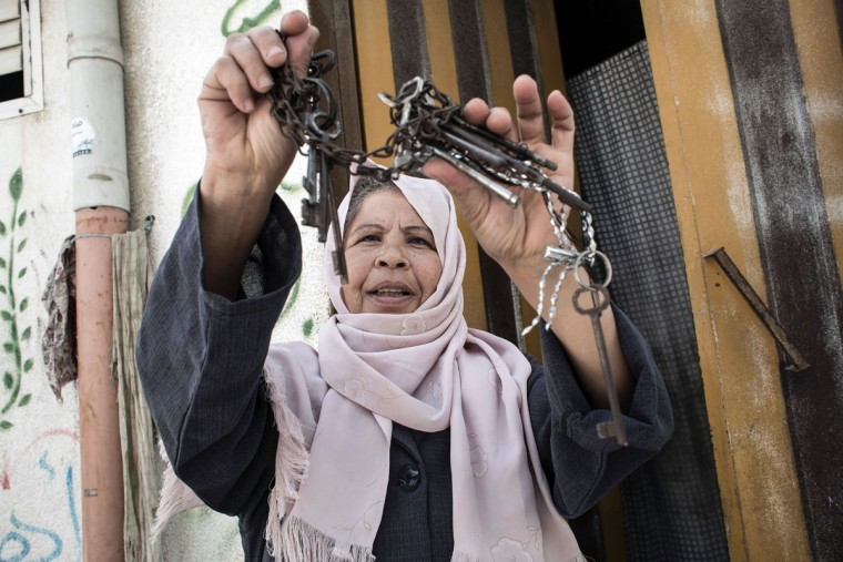 "Palestinian refugee Aisha, 53, who says is a former inhabitant of the town of Beersheva, waves a group of keys outside her home in the Khan Yunis refugee camp in the southern Gaza Strip on May 15, 2016, on the 68th anniversary of the ""Nakba"". ""Nakba"" means in Arabic ""catastrophe"" in reference to the birth of the state of Israel 68-years-ago in British-mandate Palestine, which led to the displacement of hundreds of thousands of Palestinians who either fled or were driven out of their homes during the 1948 war over Israel's creation. The key symbolises the homes left by Palestinians in 1948. (AFP PHOTO / SAID KHATIB)"