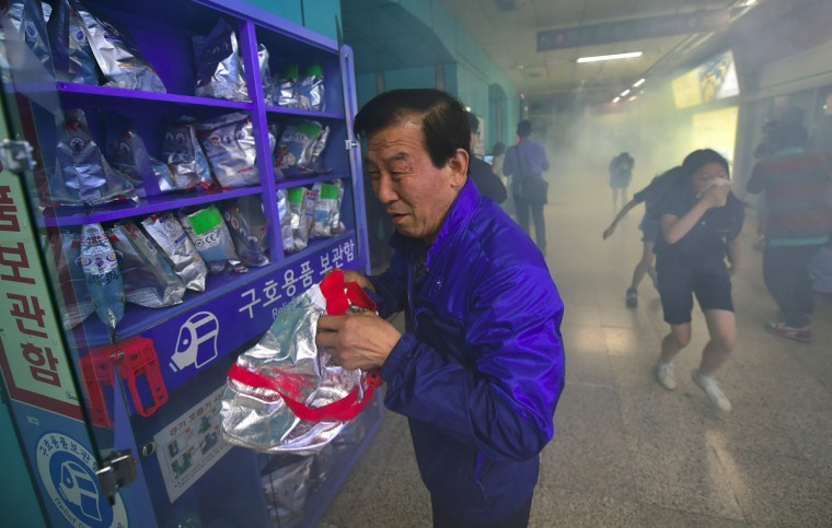 South Koreans participate in a fire drill as part of a disaster management exercise at a subway station in Seoul on May 16, 2016. (JUNG YEON-JE/AFP/Getty Images)