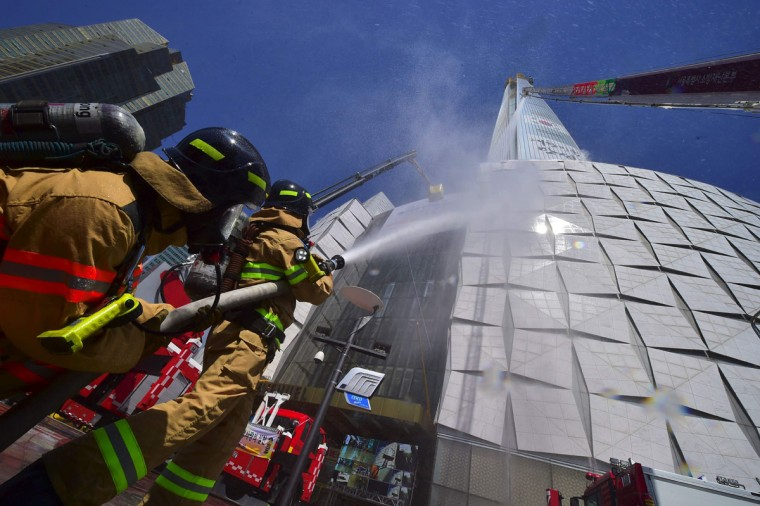 South Korean firefighters spray water during a fire drill as part of a disaster management exercise at a skyscraper in Seoul on May 16, 2016. (JUNG YEON-JE/AFP/Getty Images)