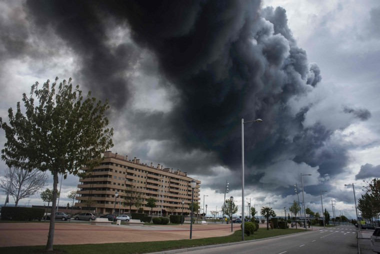 Black clouds of smoke are produced by tyres burning in an uncontrolled dump near the town of Sesena, after a fire brokeout early on May 13, 2016. A huge waste ground near Madrid where millions of tyres have been dumped was on fire today, releasing a thick black cloud of toxic fumes that officials worry could harm residents nearby. (AFP Photo/Pedro Armestre)