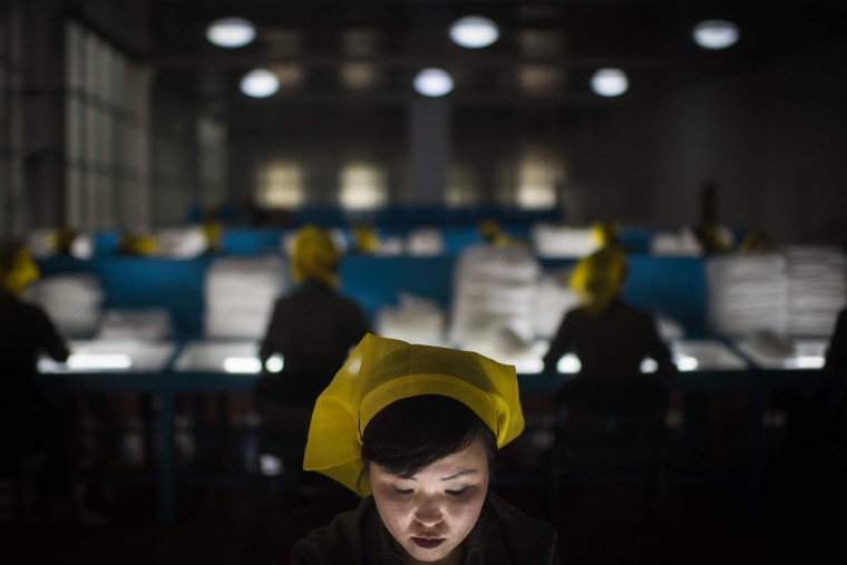 A worker sorts through silk at a silk factory in Pyongyang on May 9, 2016. (AFP PHOTO / Ed Jones)