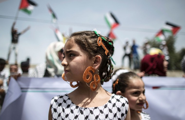 "A Palestinian girl wears earrings bearing the number ""68"" and a hair slide in the shape of a key on May 15, 2016 in Gaza city during a rally to commemorate the ""Nakba"" or ""catastrophe"" in Arabic in reference to the establishment in 1948 of the state of Israel. ""Nakba"" means in Arabic ""catastrophe"" in reference to the birth of the state of Israel 68-years-ago in British-mandate Palestine, which led to the displacement of hundreds of thousands of Palestinians who either fled or were driven out of their homes during the 1948 war over Israel's creation. The key symbolises the homes left by Palestinians in 1948. (AFP PHOTO/ MAHMUD HAMS)"