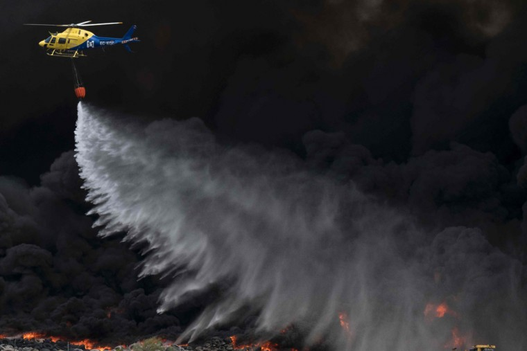 A helicopter drops water over tyres burning in an uncontrolled dump near the town of Sesena, after a fire brokeout early on May 13, 2016. A huge waste ground near Madrid where millions of tyres have been dumped was on fire today, releasing a thick black cloud of toxic fumes that officials worry could harm residents nearby. (AFP Photo/Pedro Armestre)