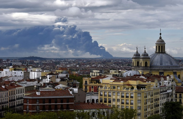 Picture taken from the Almudena cathedral in Madrid shows a huge smoke column caused by a fire in an uncontrolled dump near the town of Sesena, on May 13, 2016. A huge waste ground near Madrid where millions of tyres have been dumped was on fire today, releasing a thick black cloud of toxic fumes that officials worry could harm residents nearby. (AFP Photo/Gerard Julien)