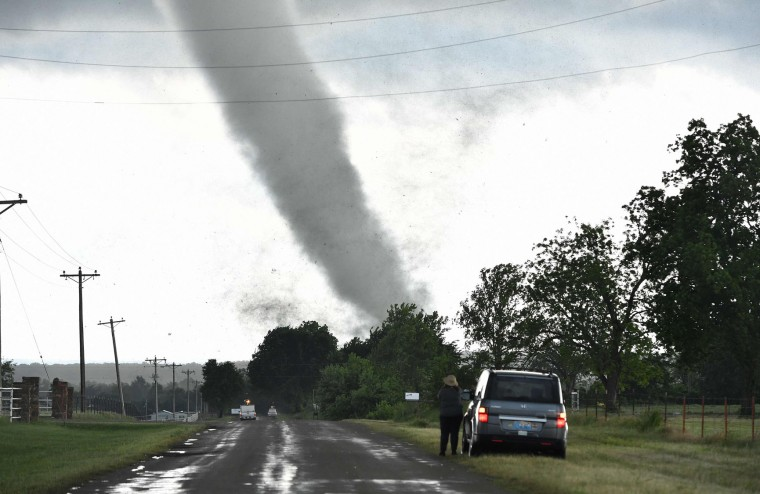 A woman looks on while a tornado rips through a residential area after touching down south of Wynnewood, Oklahoma on May 9, 2016. (Josh Edelson/AFP/Getty Images)