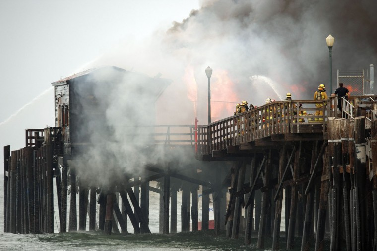 Firefighters contend with a fire burning on the Seal Beach pier in Seal Beach, Calif. on Friday, May 20, 2016. The blaze erupted early Friday at the end of the long wooden pier southeast of Los Angeles. Smoke was pouring out of holes in the roof, much of which had collapsed. The restaurant has been closed since 2013. (Ken Steinhardt/The Orange County Register via AP)