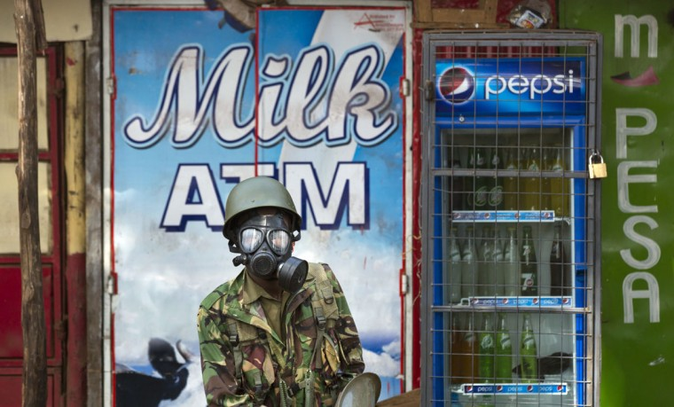 A Kenyan policeman wears a gas mask as he stands in from of a milk dispenser at a kiosk, during running battles between police firing tear gas and protesters throwing rocks, in the Kibera slum of Nairobi, Kenya Monday, May 23, 2016. Kenya's police shot, beat and tear gassed opposition demonstrators across the country who tried to gather to call for the electoral commission to be dissolved due to allegations of bias and corruption. (AP Photo/Ben Curtis)