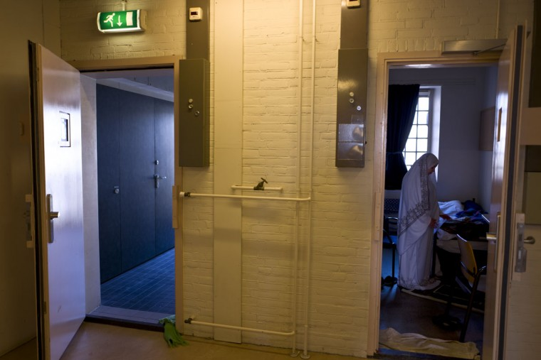 Iraqi refugee Fatima Hussein, 65, prays inside her room at the former prison of De Koepel in Haarlem, Netherlands. With crime declining in the Netherlands, the country is looking at new ways to fill its prisons. (AP Photo/Muhammed Muheisen)