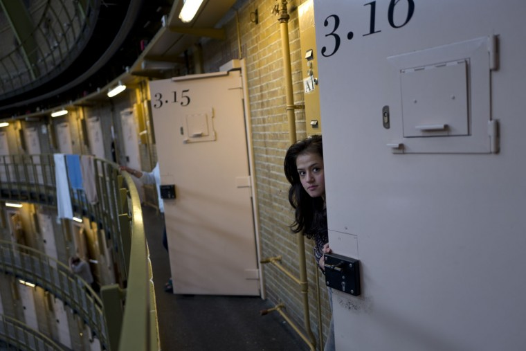 Afghan refugee Shazia Lutfi, 19, peeks through the door of her room at the former prison of De Koepel in Haarlem, Netherlands. The government has let Belgium and Norway put prisoners in its empty cells and now, amid the huge flow of migrants into Europe, several Dutch prisons have been temporarily pressed into service as asylum seeker centers. (AP Photo/Muhammed Muheisen)