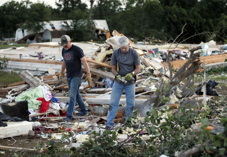 Kenny Baker, right, and Tony Scheuerman help to clean up after a tornado destroyed the home of Lisa Buckner, not pictured, west of Wynnewood, Okla., in rural Gavin County, Monday, May 9, 2016. Storms swept through the nation's midsection Monday, spawning numerous tornadoes. (Nate Billings/The Oklahoman via AP)