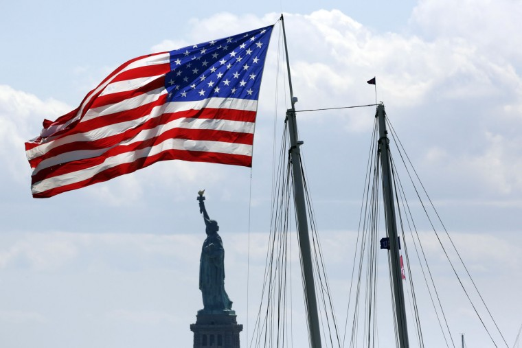 A spectator's sailboat flies a United States flag near the Statue of Liberty during an America's Cup sailing event, Sunday, May 8, 2016, on the Hudson River in New York. (AP Photo/Mark Lennihan)
