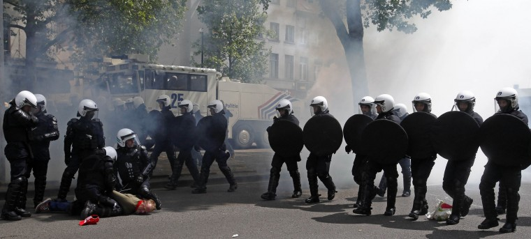 Police detain a man during clashes with demonstrators at a protest against new working regulations in Brussels, Belgium, Tuesday, May 24, 2016. Belgian riot police fired a water cannon at protesters Tuesday after fighting broke out at the end of a major anti-austerity demonstration attended by tens of thousands of people in central Brussels. (AP Photo/Michel Spingler)