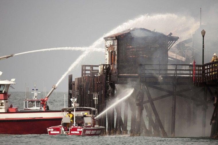 Fireboats from Long Beach hit the fire inside the closed Ruby's Diner at the end of the Seal Beach pier in Seal Beach, Calif. on Friday, May 20, 2016. The blaze erupted early Friday at the end of the long wooden pier southeast of Los Angeles. Smoke was pouring out of holes in the roof, much of which had collapsed. The restaurant has been closed since 2013. (Ken Steinhardt/The Orange County Register via AP)