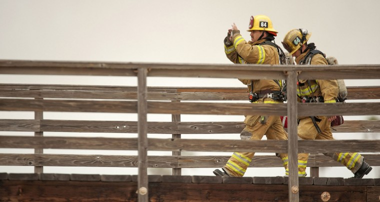 A firefighter takes pictures as he approaches the end of the Seal Beach Pier as a fire burns inside the closed Ruby's Diner on Friday, May 20, 2016. The blaze erupted early Friday at the end of the long wooden pier southeast of Los Angeles. Smoke was pouring out of holes in the roof, much of which had collapsed. The restaurant has been closed since 2013. (Ken Steinhardt/The Orange County Register via AP)