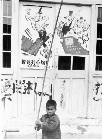 In this file photo taken May 27, 1967, a child plays with a bamboo pole near government posters that attacks then Chinese president Liu Shaoqi as anti-Maoist during the cultural revolution in Shanghai, China. Poster at right urges support of the revolution. Monday, May 16, 2016 marks the 50th anniversary of a 1966 party meeting that spearheaded the 10-year Cultural Revolution, a violent and frequently chaotic attempt by Mao to reassert his power and revive his party's egalitarian ideals. (AP Photo, File )