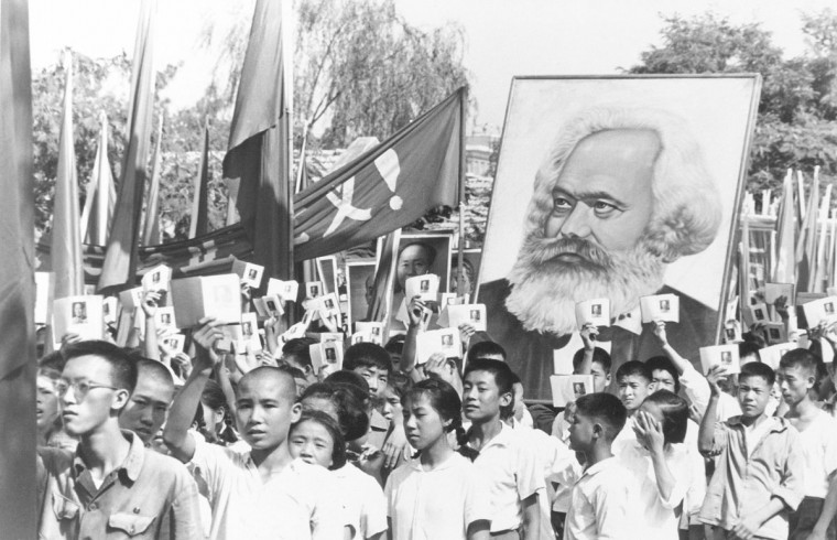 In this file photo taken Sept. 14, 1966, youths are seen at a rally during the height of the Red Guard upheaval waving copies of the collected writings of Communist Party Chairman Mao Zedong, often referred to as Mao's Little Red Book and carrying a poster of Karl Marx. On May 16, 1966, the Communist Party's Politburo produced a document announcing the start of what was formally known as the Great Proletarian Cultural Revolution to pursue class warfare and enlist the population in mass political movements. Launched by leader Mao Zedong, it set off a decade of tumult to revive communist goals and enforce a radical egalitarianism. (AP Photo, File)