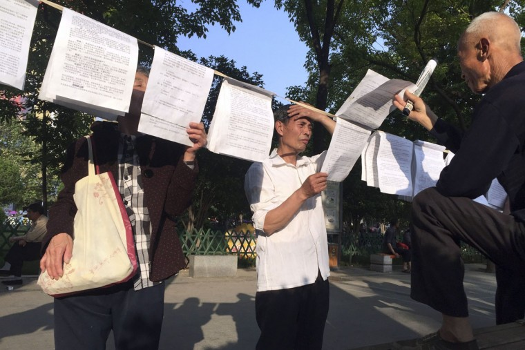In this photo taken Sunday, May 1, 2016, men read essays pinned on a clothesline, condemning the past 30 years of liberalization or positively reappraising the Cultural Revolution at Zhouwangcheng Plaza in Luoyang in central China's Henan province. In the ancient city of Luoyang, the old, the poor and the marginalized gather daily in the main public square to profess nostalgia for the decade-long political movement, while downplaying that period's violent excesses. (AP Photo/Ng Han Guan)