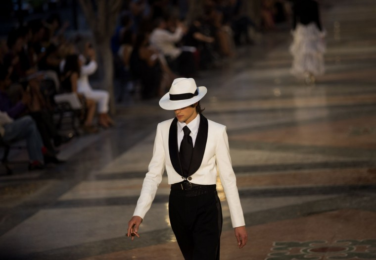 "A model wears a creation from the Karl Lagerfeld ""cruise"" line for fashion house Chanel, at the Paseo del Prado street in Havana, Cuba, Tuesday, May 3, 2016. With the heart of the Cuban capital effectively privatized by an international corporation under the watchful eye of the Cuban state, the premiere of Chanel 2016/2017 ""cruise"" line offered a startling sight in a country officially dedicated to social equality and the rejection of material wealth. (AP Photo/Ramon Espinosa)"